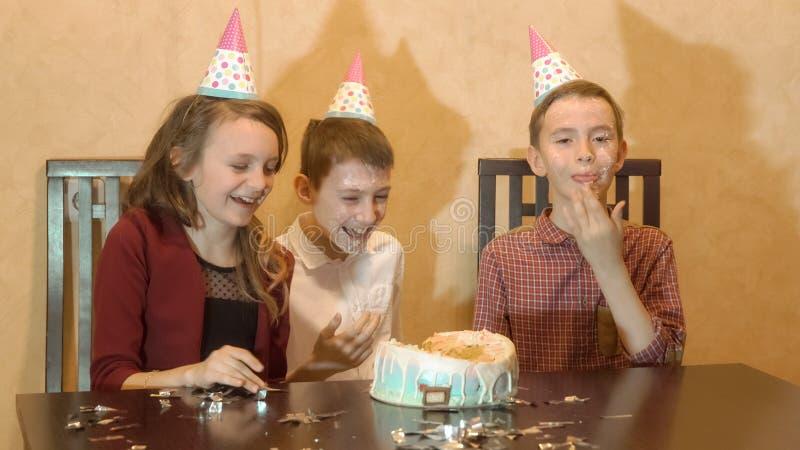 Bambini spensierati ad una festa di compleanno gli amici dunked affrontano nella torta di compleanno fotografia stock libera da diritti