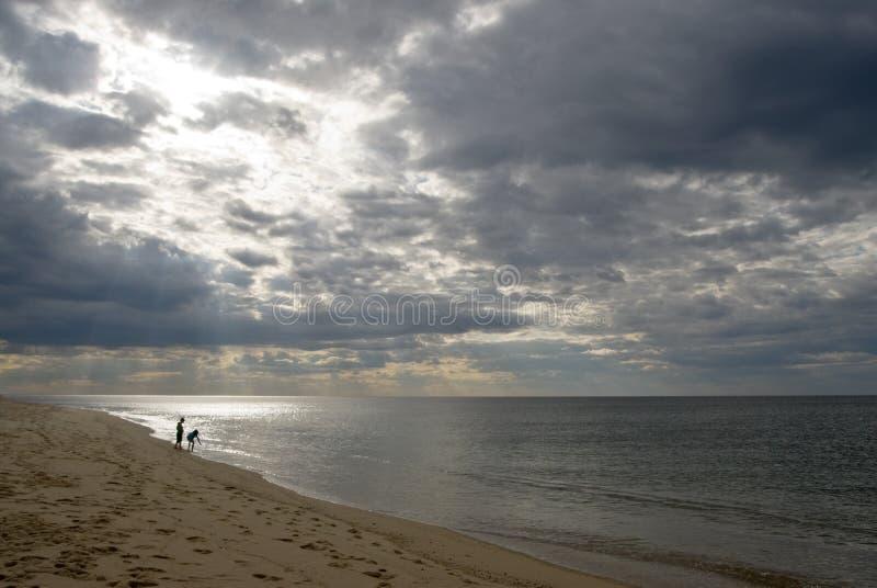Bambini sulla spiaggia, cielo drammatico, nubi tempestose fotografia stock libera da diritti