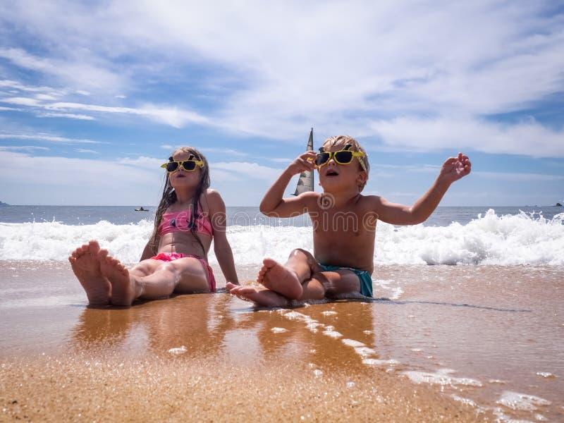 Bambini sulla spiaggia: Un ragazzo e una ragazza in occhiali da sole divertenti stanno sedendo sulla spiaggia nella schiuma del m immagini stock libere da diritti