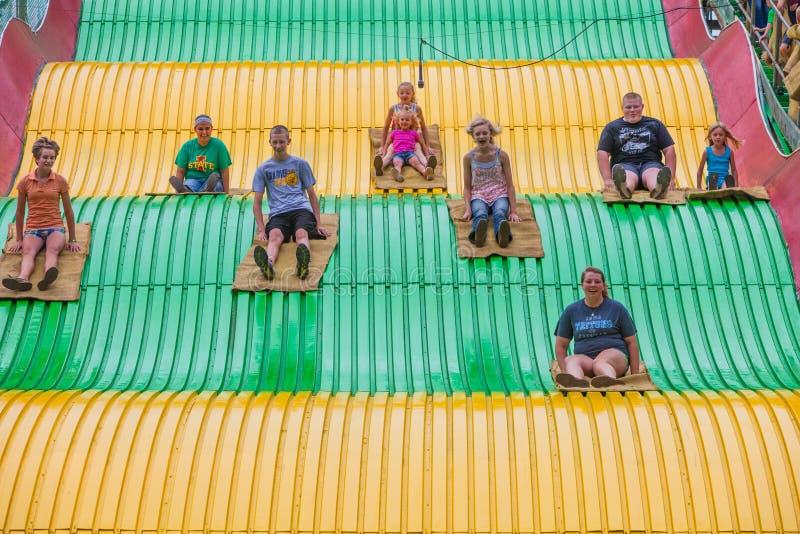 Bambini sullo scorrevole di carnevale allo stato giusto fotografia stock libera da diritti