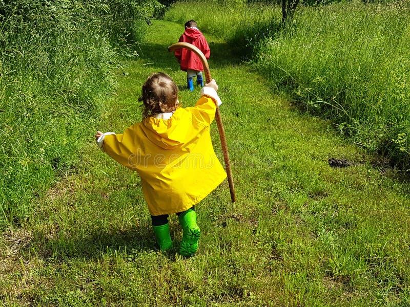 Bambini svegli che corrono sulla strada aziendale con il bastone fotografia stock libera da diritti