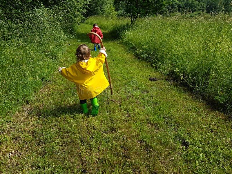 Bambini svegli che corrono sulla strada aziendale con il bastone fotografia stock