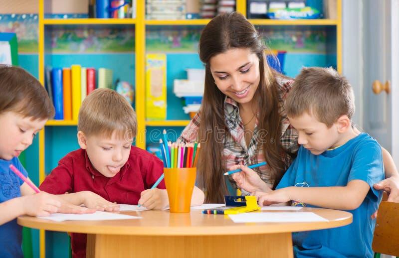 Bambini svegli che disegnano con l'insegnante alla classe prescolare fotografie stock