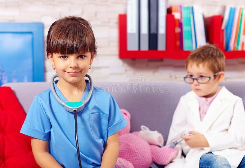 Bambini svegli che giocano al dottore con i giocattoli fotografia stock libera da diritti