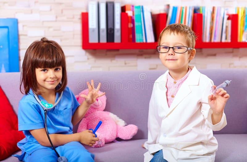 Bambini svegli che giocano in medici con gli strumenti del giocattolo fotografia stock libera da diritti