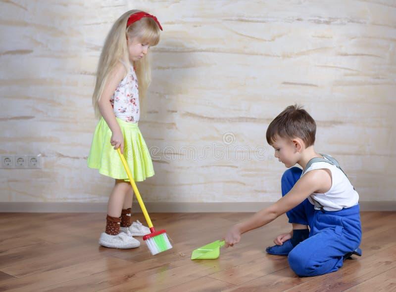 Bambini svegli che usando la scopa e paletta per la spazzatura del giocattolo fotografia stock