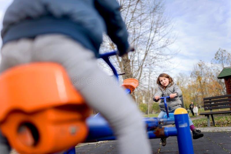 Bambini svegli divertendosi sul movimento alternato al campo da giuoco fotografia stock libera da diritti