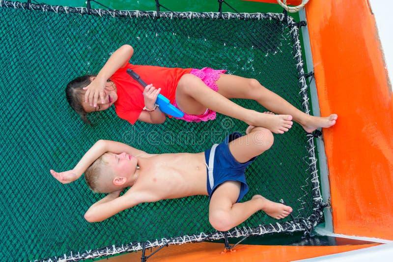 Bambini svegli su un viaggio della barca La ragazza sta giocando una chitarra del giocattolo per la sua f fotografia stock