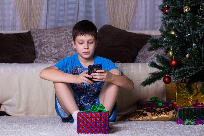 bambini, tecnologia, comunicazione di Internet e concetto della gente - ragazzo con il messaggio mandante un sms dello smartphone fotografia stock libera da diritti