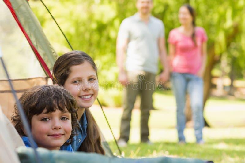 Bambini in tenda con le coppie nel fondo al parco fotografie stock libere da diritti
