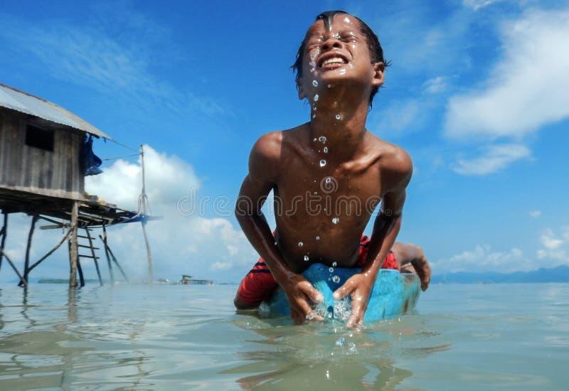Bambini tribali di Bajau divertendosi saltando nel mare dalla loro barca, Sabah Semporna, Malesia fotografie stock libere da diritti