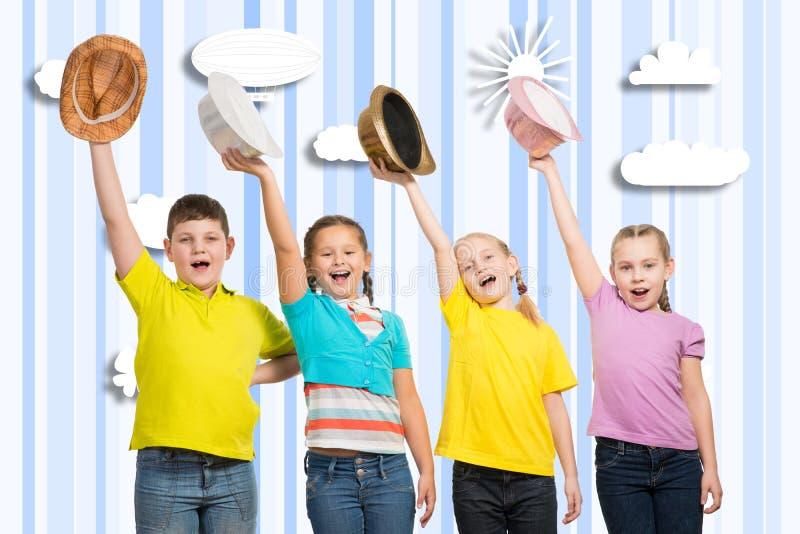 Bambini in una fila, portante un cappello fotografie stock