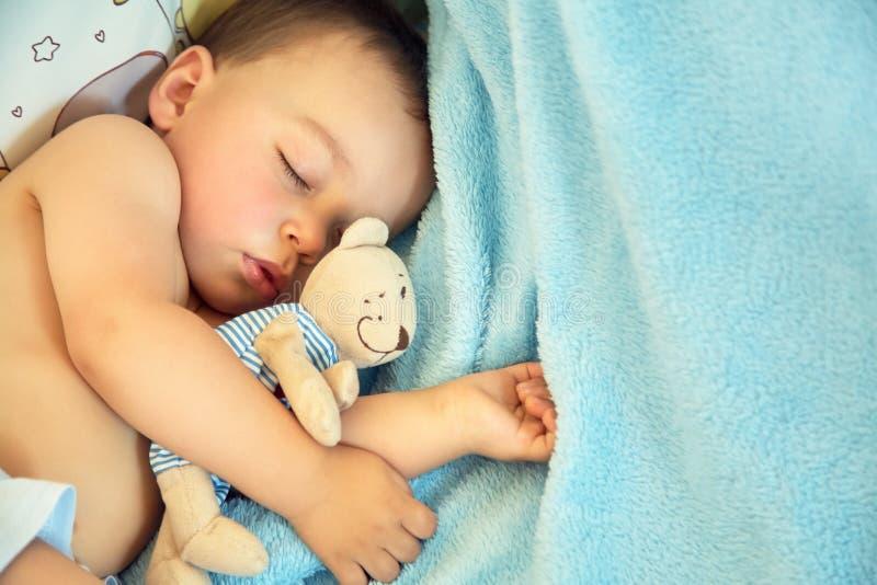 Bambino addormentato con un orso molle del giocattolo ragazzino che si trova in greppia su una coperta blu fotografie stock