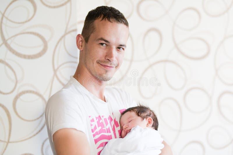 Bambino addormentato nelle armi di suo padre Ritratto di giovane padre che tiene suo figlio del neonato a casa fotografia stock