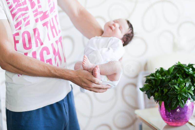 Bambino addormentato nelle sue armi Padre che tiene sua figlia del neonato dopo la nascita sulle armi , Concetto di amore e famig fotografie stock libere da diritti