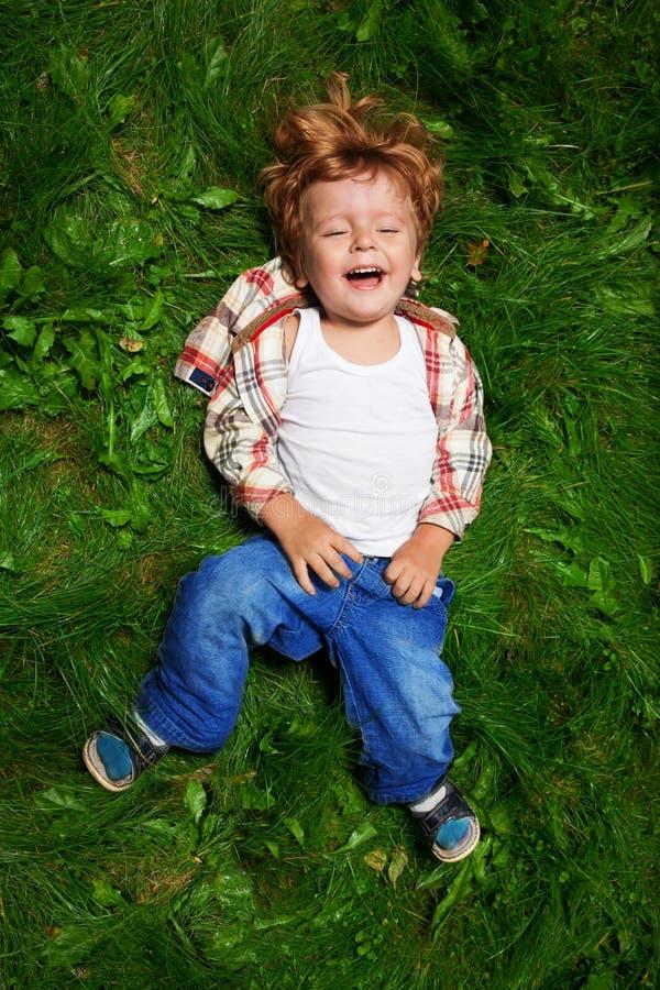 Bambino adorabile che ride sull'erba fotografia stock