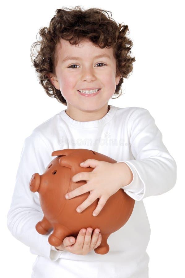 Bambino adorabile con il suo risparmio in suo contenitore di soldi di piggy immagini stock