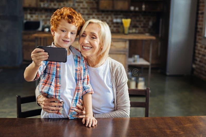 Bambino adorabile della testarossa che prende selfie con la nonna immagine stock libera da diritti