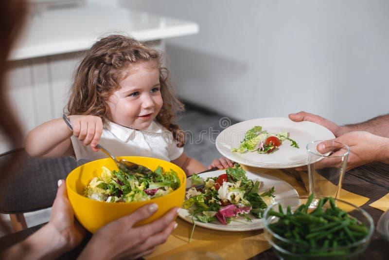 Bambino affamato che mangia le verdure con la mamma ed il papà immagine stock