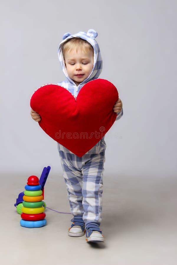 Bambino affascinante che tiene un cuore rosso in mani immagine stock libera da diritti