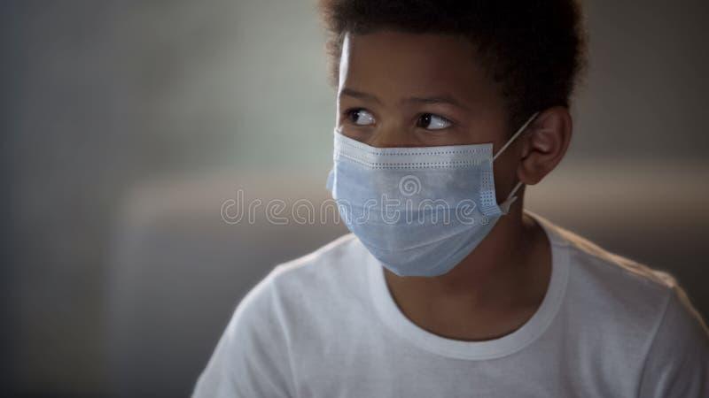 Bambino africano in camicia bianca che indossa maschera protettiva, paziente ricoverato, medicina immagini stock