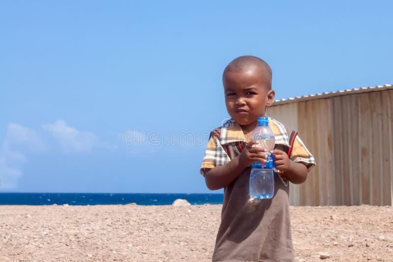 Bambino africano sveglio con la bevanda della bottiglia di acqua fotografia stock libera da diritti