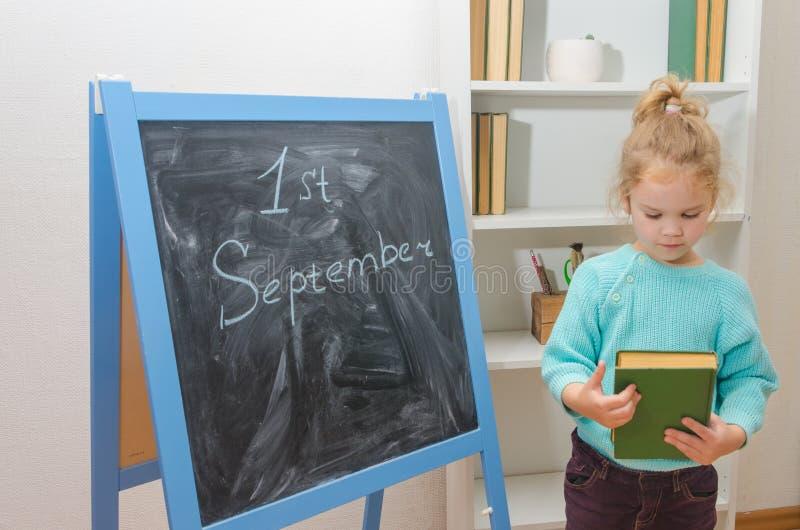 Bambino al bordo di gesso con l'iscrizione il 1° settembre e fotografia stock libera da diritti