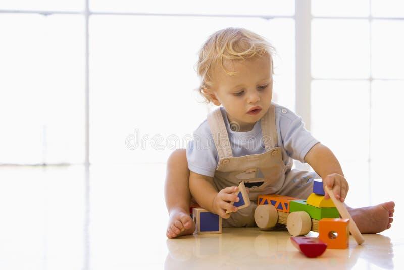 Bambino all'interno che gioca con il camion del giocattolo fotografie stock