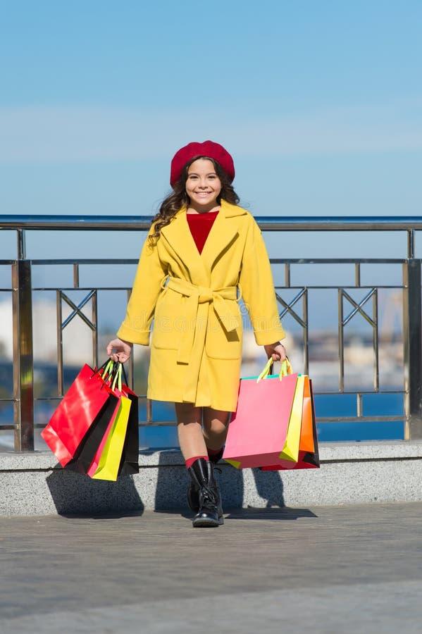 Bambino alla moda in berretto e cappotto francesi di caduta Tendenza di autunno Giorno di acquisto Bambina felice Bambina con acq immagine stock libera da diritti