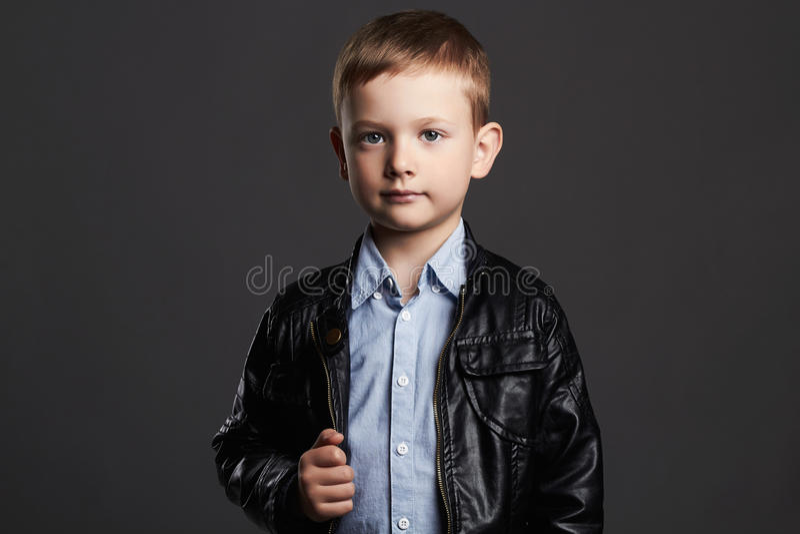 Bambino alla moda in cappotto di cuoio Ragazzino alla moda 6 anni divertenti del bambino immagine stock