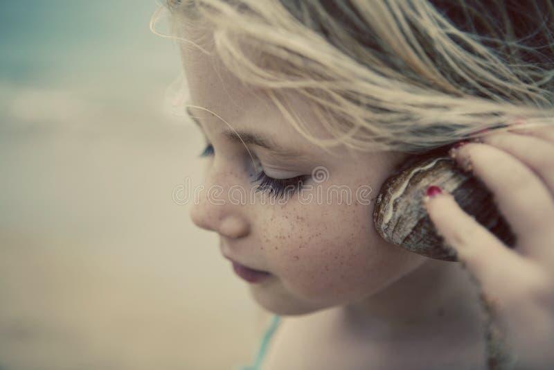 Bambino alla spiaggia con il Seashell fotografie stock libere da diritti