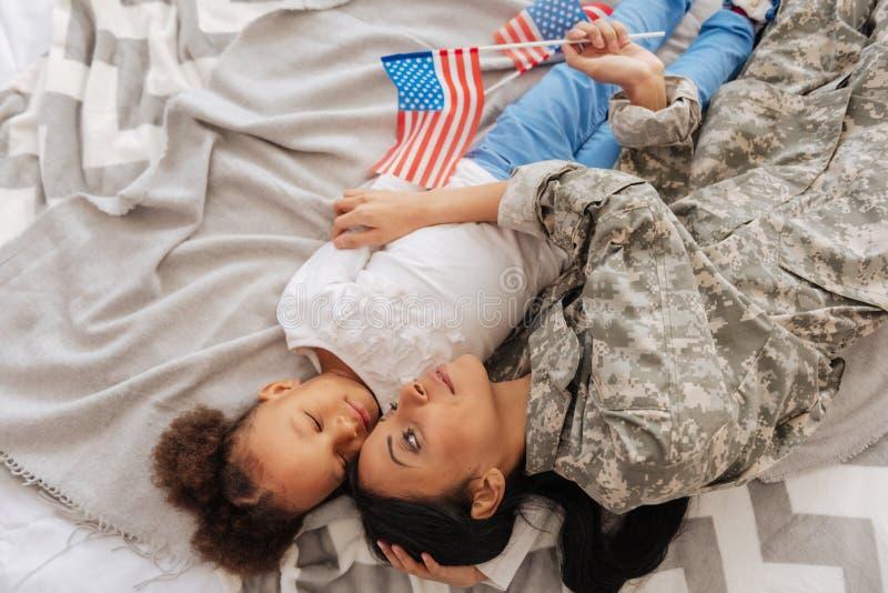 Bambino allegato grazioso e sua la mamma che riposano a letto immagini stock