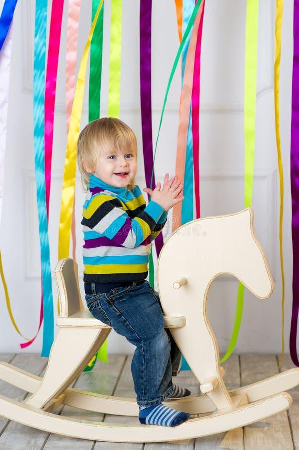 Bambino allegro che monta cavallo di legno fatto a mano fotografia stock libera da diritti