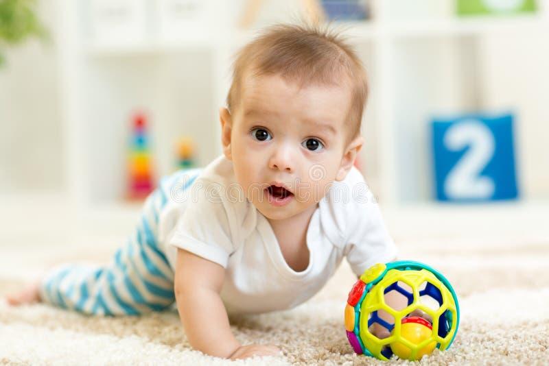Bambino allegro che striscia sul pavimento nella stanza della scuola materna immagini stock