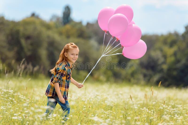 bambino allegro con i palloni rosa a disposizione che corre fotografie stock