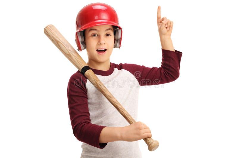 Bambino allegro con l'attrezzatura di baseball che indica su fotografia stock
