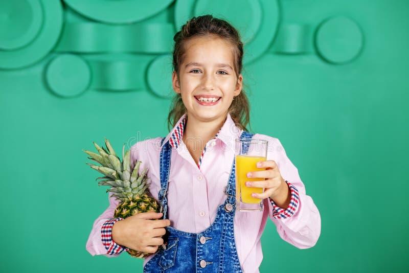 Bambino allegro con succo e l'ananas utili Il concetto della a fotografia stock libera da diritti