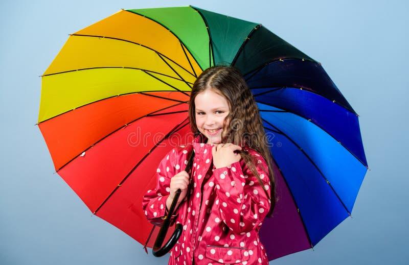 bambino allegro dei pantaloni a vita bassa nell'umore positivo Protezione di pioggia Rainbow piccola ragazza felice con l'ombrell fotografia stock