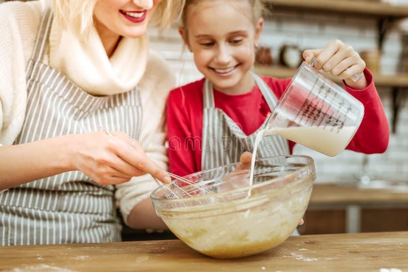 Bambino allegro felice che aggiunge latte dalla tazza di misurazione immagine stock