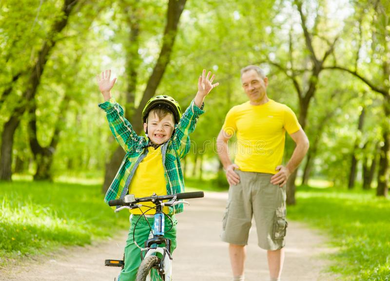 Bambino allegro su una bicicletta con suo nonno nel parco fotografie stock