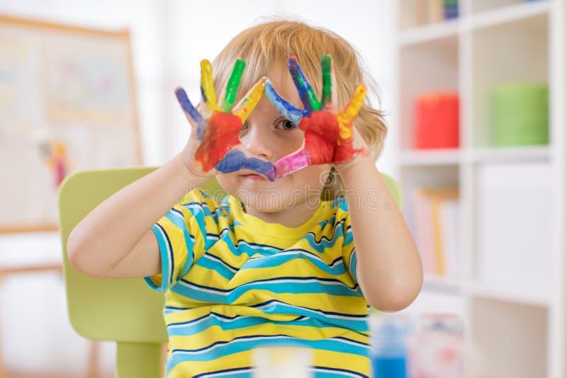Bambino allegro sveglio con le mani dipinte nei colori luminosi fotografia stock libera da diritti