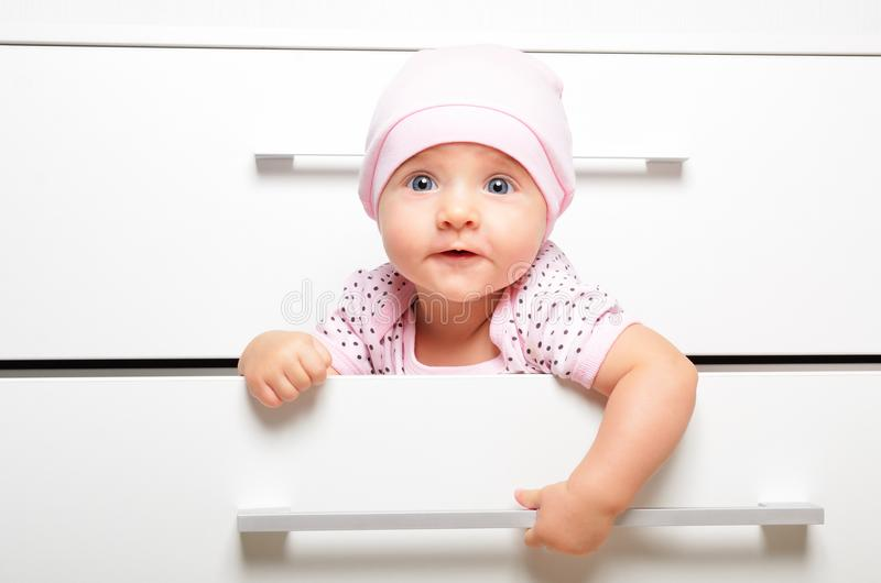 Bambino allegro sveglio, sedentesi in un petto del cassetto fotografia stock libera da diritti