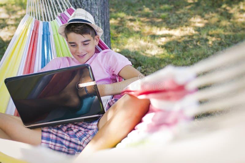 Bambino in amaca con il computer immagini stock libere da diritti