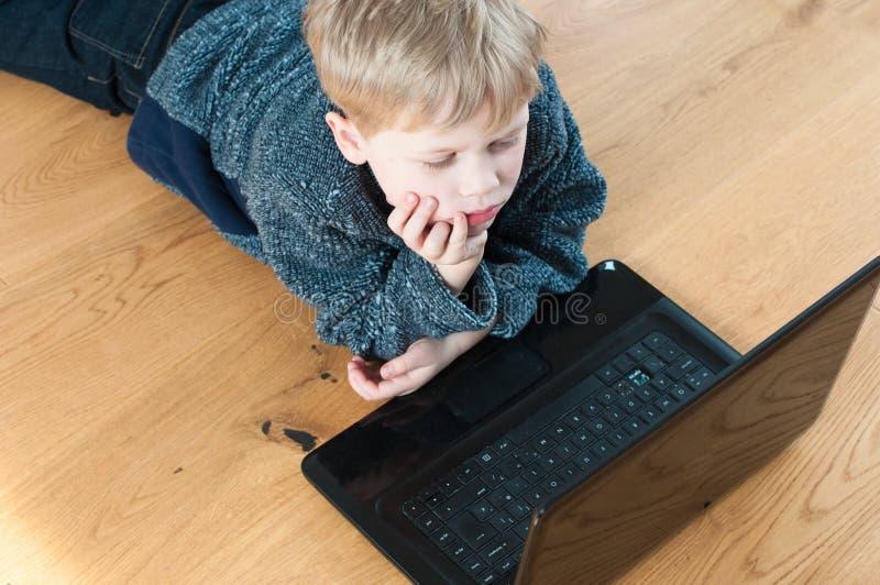 Bambino annoiato che esamina i siti Web online fotografia stock