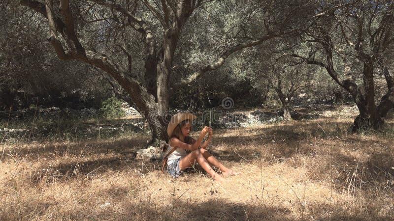 Bambino annoiato che gioca nella ragazza di Olive Orchard Meditative Kid Little che si rilassa dall'albero immagini stock libere da diritti