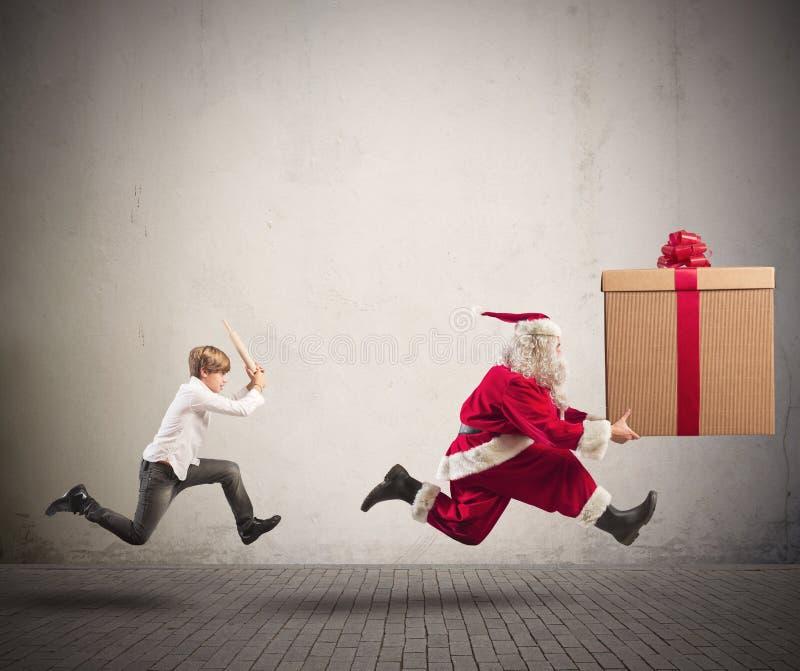 Bambino arrabbiato che insegue Santa Claus fotografia stock libera da diritti
