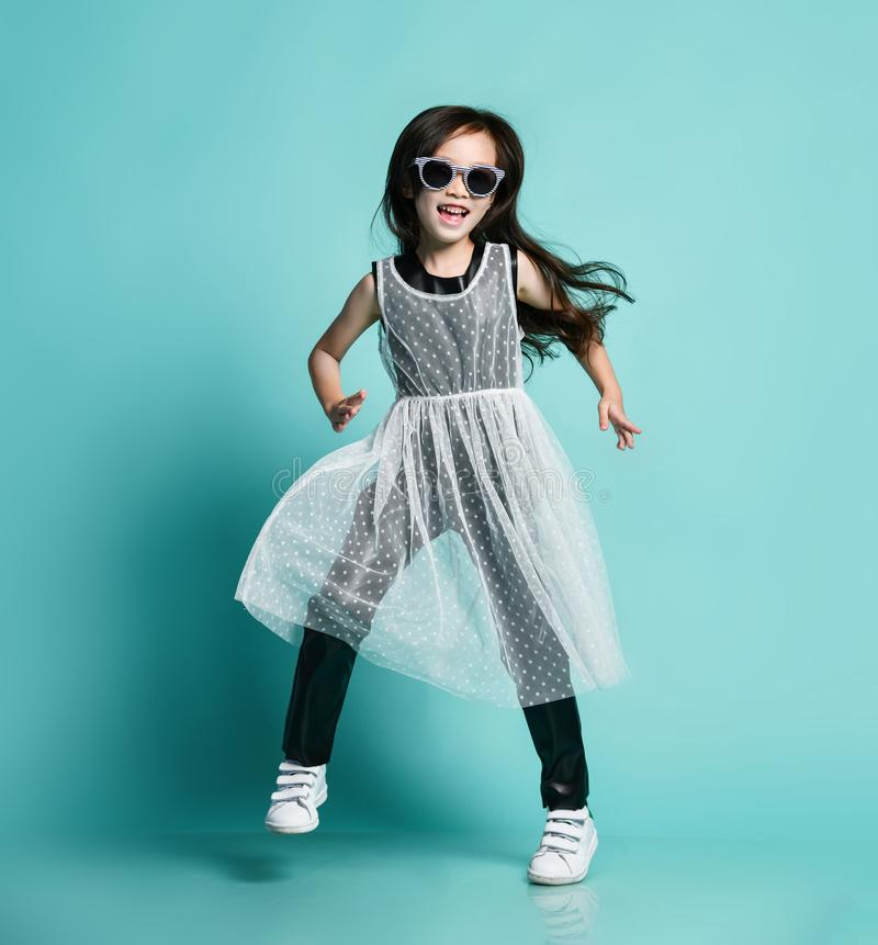 Bambino asiatico alla moda allegro della neonata in vestiti in bianco e nero moderni e nei balli degli occhiali da sole a diverti immagine stock libera da diritti