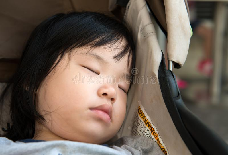 Bambino asiatico che dorme in passeggiatore immagini stock libere da diritti