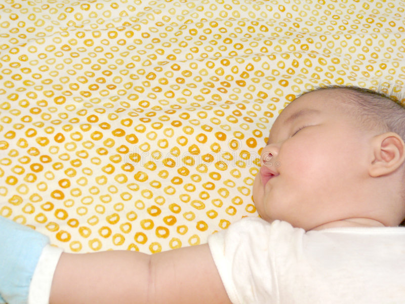 Bambino asiatico che dorme sul lato con il braccio allungato fotografie stock