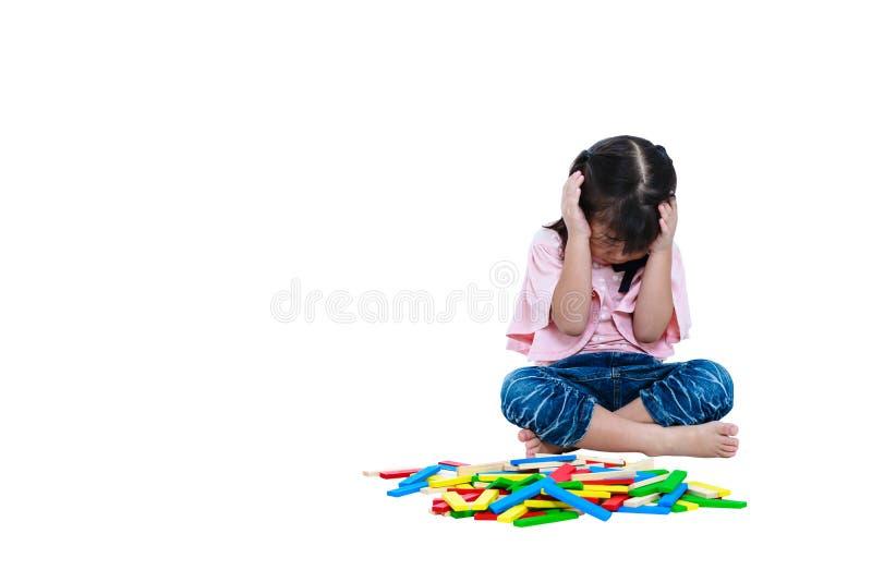 Bambino asiatico che gioca i blocchetti di legno del giocattolo Ragazza triste che grida e che mostra immagini stock
